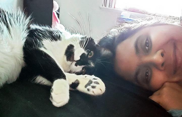 Smiling Ana Merkulova lying head-to-head next to black and white cat