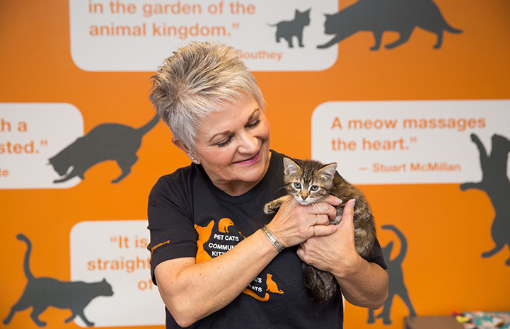Volunteer Becky Anderson holding a small tabby kitten in front of a wall with cat quotes