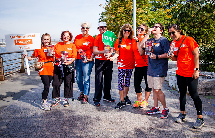 Group of volunteers wearing orange T-shirts working a treat station during a Strut Your Mutt event