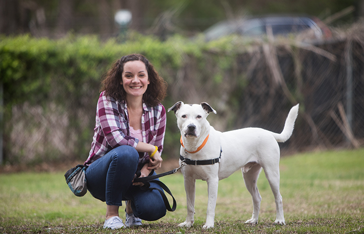 Volunteer Lisa McManus crouching on the ground next to Micah, a white pit bull terrier who is standing and looking at the camera