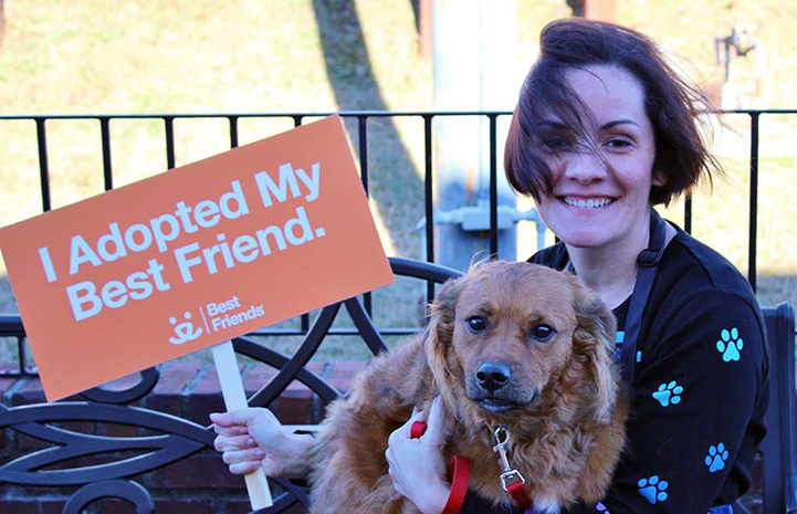 Volunteer Lisa McManus with a brown dog in her lap holding a sign that says, I adopted my best friend