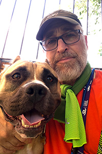 Volunteer David Glazer wearing a green scarf and taking a selfie with a big brown dog