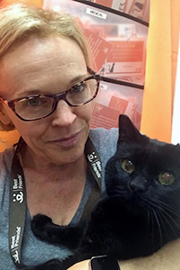 Belle Henderson the volunteer holding a black cat