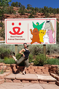 Volunteer Chelsea Eng in front of the Best Friends sign by the Welcome Center