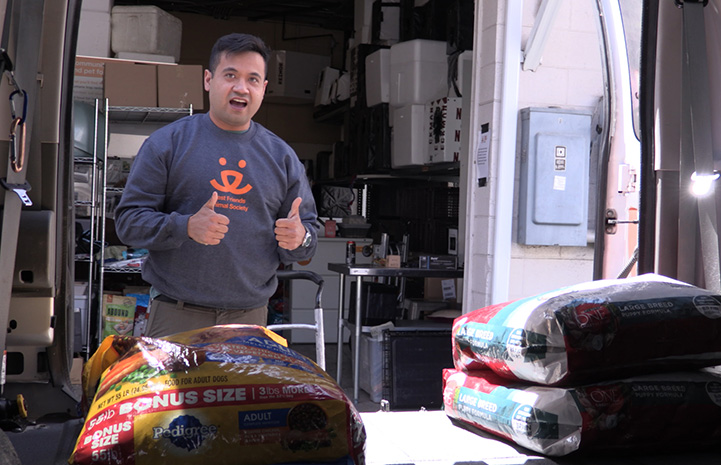 Volunteer Christian Ordonez wearing a Best Friends sweatshirt giving a thumbs up from behind some large bags of dog food