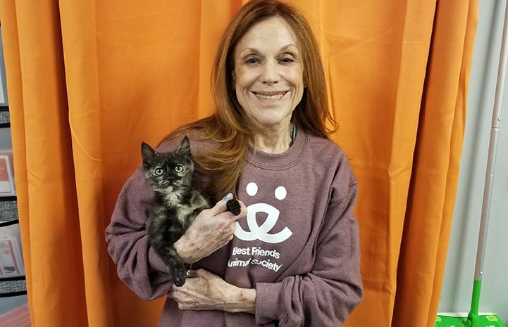 Volunteer Connie Murphy wearing a Best Friends sweatshirt and holding a tortoiseshell kitten