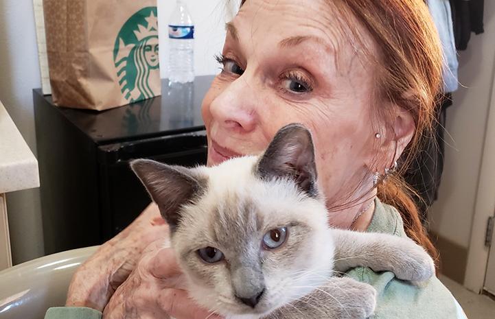 Connie Murphy holding Siamese cat, Nicodemus