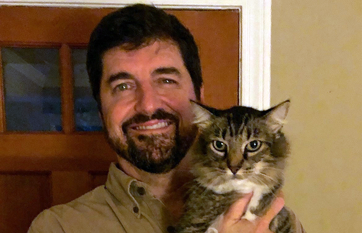 Volunteer Daniel Pruitt holding a brown tabby cat