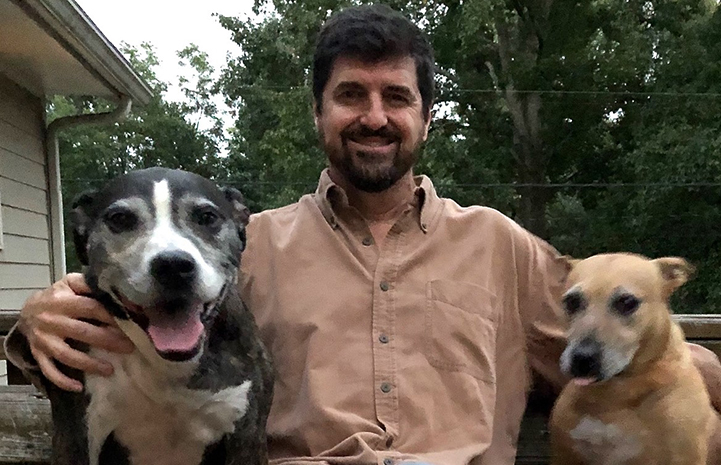 Volunteer Daniel Pruitt surrounded by two dogs