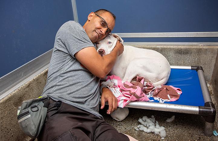 Volunteer Robert Lobo lying on a dog bed hugging Delilah the dog in a kennel