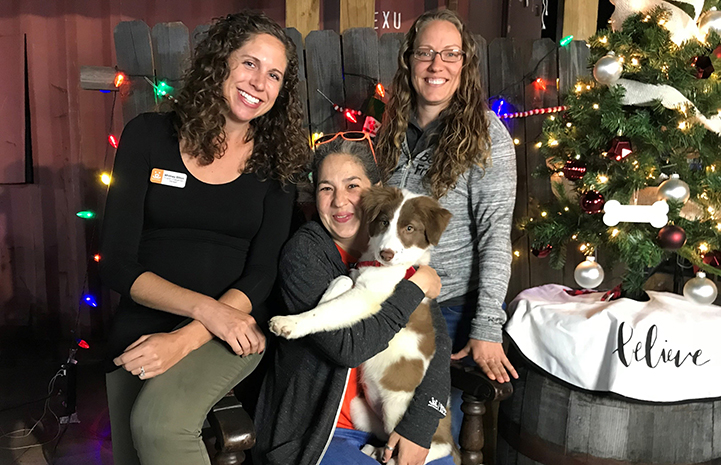 Deya Galvan holding a puppy with Amy Kohlbecker and Whitney Bliton, next to a small Christmas tree