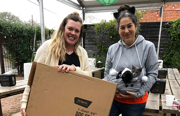 Volunteer Deyra Galvan wearing cat ears with another woman holding a box and a litter of kittens
