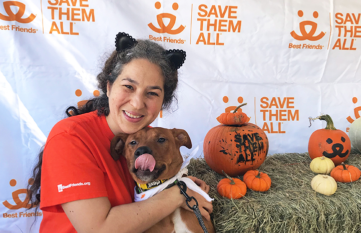 Volunteer Deyra Galvan wearing cat ears and hugging a dog who is licking his lips, next to some pumpkins