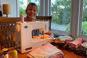 Volunteer Gilly sitting at a sewing machine making masks