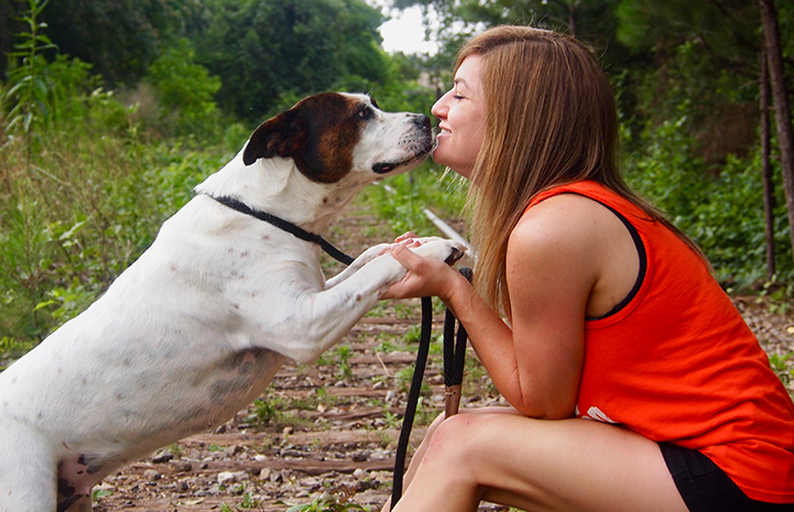 Volunteer Jamie Serratell holding the paws and looking face-to-face with a white and brown dog
