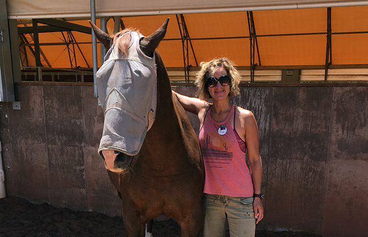 Jennifer Wesely next to a horse wearing a fly mask at Horse Haven