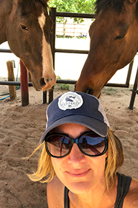 Jennifer Wesely volunteering at Horse Haven with two horses behind her