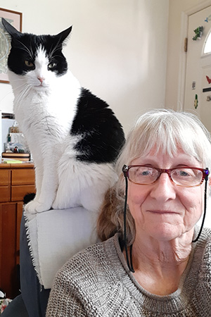 Volunteer Judy Steiger sitting next to a black and white cat