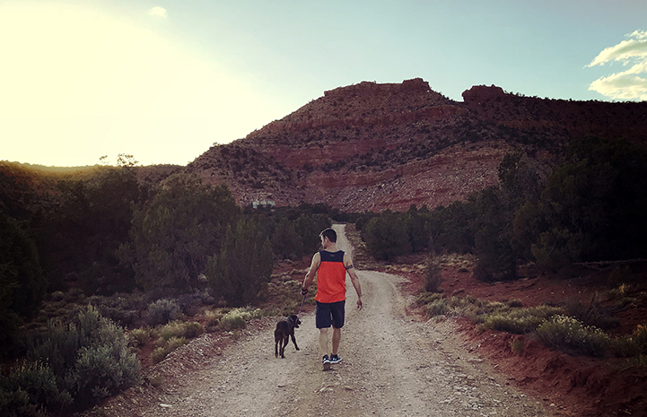 Volunteer Kevin Wesely walking Jarvis the dog toward a red cliff