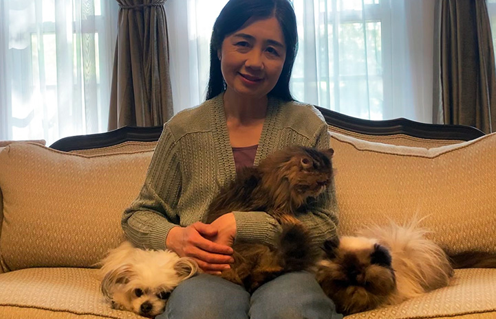 Kyoko Bruguera sitting on a couch with her two pet cats and dog