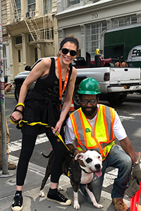 Volunteer Lauren Fishman walking a black and white dog while standing next to a man wearing a hard hat and bright yellow safety vest
