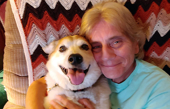 Volunteer Kathy Posekel hugging a tan and white dog with an afghan blanket behind them