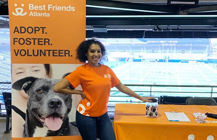 Volunteer Nisha Gross wearing an orange Best Friends T-shirt and standing at a Best Friends booth