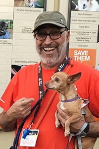Volunteer David Glazer smiling and holding a Chihuahua mix dog