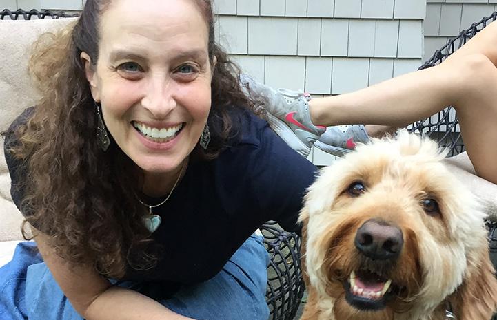 Volunteer Randi Schey posing next to a Labradoodle type dog
