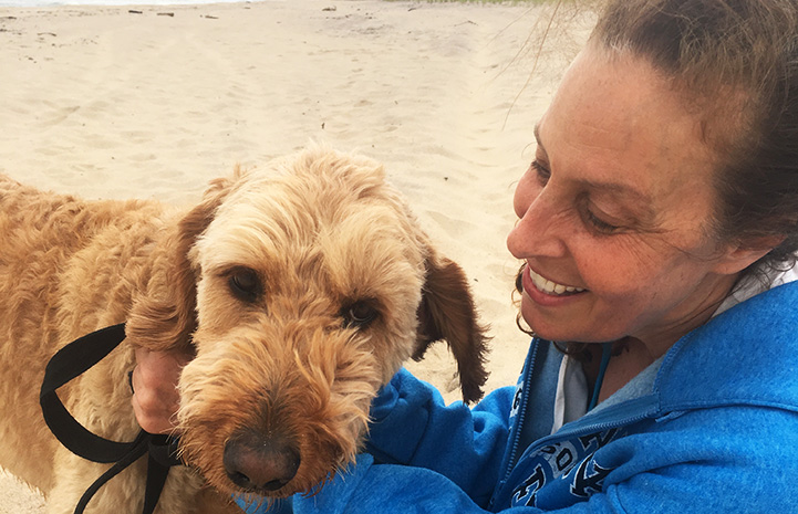 Volunteer Randi Schey at a beach with a Labradoodle type dog