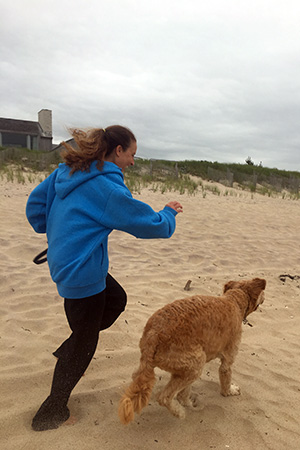 Volunteer Randi Schey running on the beach with a dog