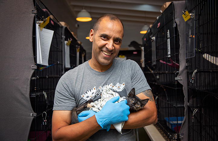 Volunteer Robert Lobo cradling a kitten in his arms standing in front of kennels