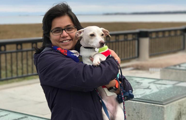 Volunteer Swarnima Singh holding her dog Brodie at the beach