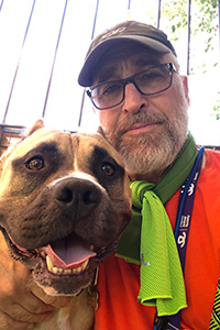 Volunteer David Glazer next to Beefy the dog