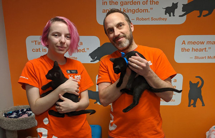 Volunteers Bella and Justin Brodie each holding black kittens while standing in front of an orange wall with graphics