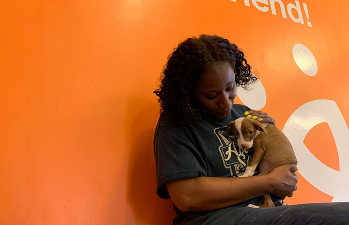 Volunteer Faye Robinson cradling a small puppy against her chest with an orange Best Friends wall behind her