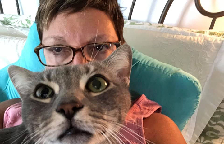 Volunteer Tracey Paige posing in a selfie with a gray tabby cat in front of her