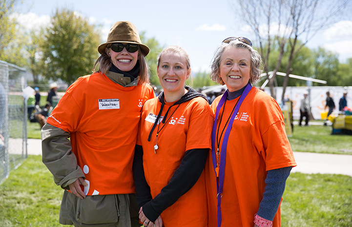 Three female volunteers wearing bright orange T-shirts posing together