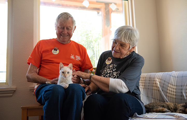Narnia the flamepoint Siamese cat sitting on the lap of Vann, who is sitting on a couch next to his wife Mary Rose