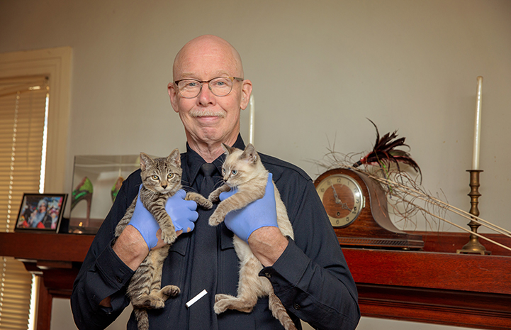 Michael Moran holding two foster kittens, while standing in front of a mantle