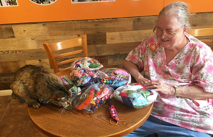Marilyn Mott sitting at a table holding the bags of mouse-shaped cat toys she made and donated, while torbie cat is ready to pounce on one