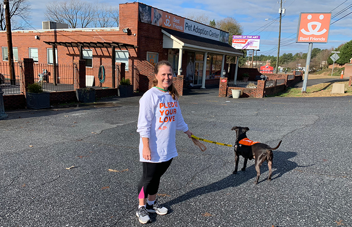 Volunteer Sandy Saffold with a dog in front of the Best Friends Lifesaving Center in Atlanta
