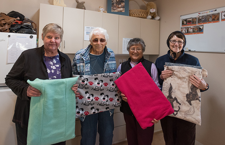 Group of four volunteers holding the blankets they'd sewed for Bunny House