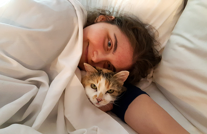 Volunteer Heather Slattery snuggled in bed with Eunice the cat on a sleepover
