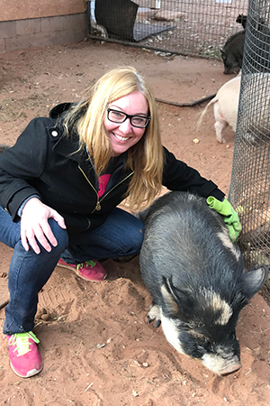 Volunteer Leila Botsford petting Petunia the pig
