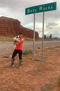 Becky McCrea holding her dog Arnie in front of a Baby Rocks road sign with cliffs in the background