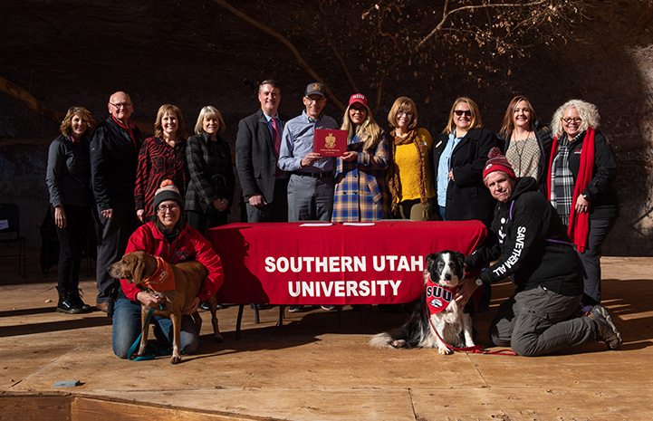 Group of people and a dog posing with a Southern Utah University banner