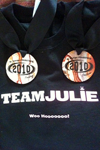 Two marathon medals on top of a Team Julie shirt