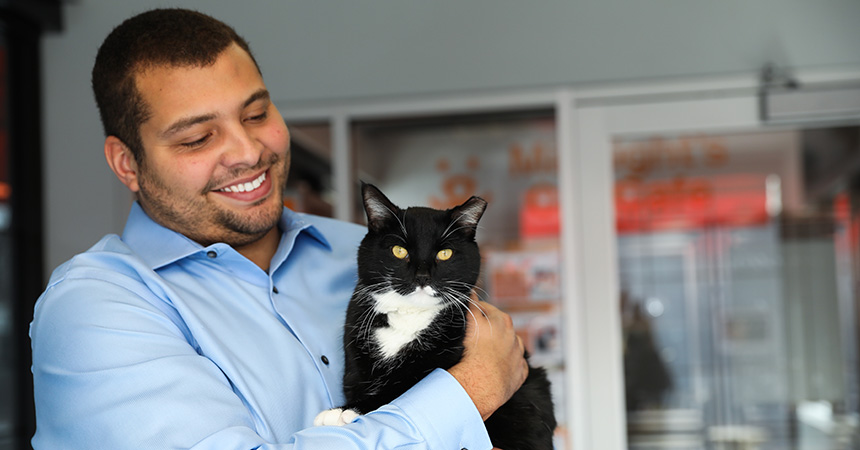 Smiling man holding a black and white cat in his arms