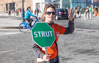 https://bestfriends.org/Female%20Strut%20Your%20Mutt%20volunteer%20holding%20a%20sign%20that%20says%20%22Strut.%22